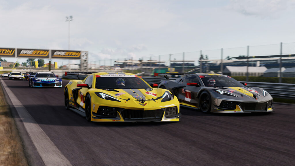 Two Corvette racing cars, one yellow and one grey, drive towards the camera at speed.