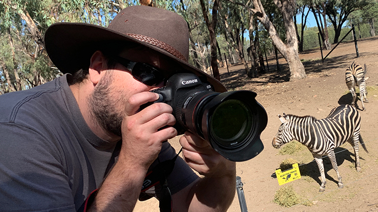 Portrait of Matthew Hatton, wearing his Akubra hat and holding his camera up to his face. In the background there are zebras.