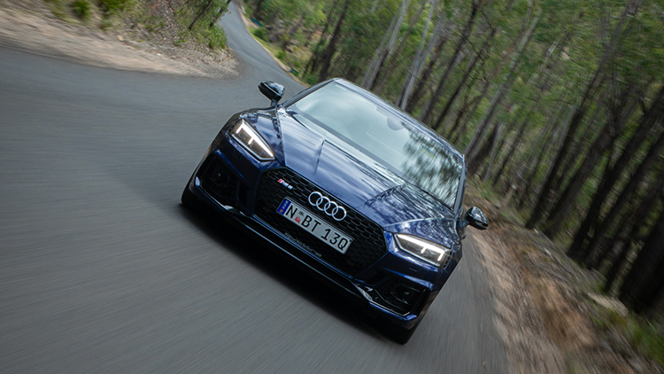 Audi RS5 front on driving on road looking back from leading car