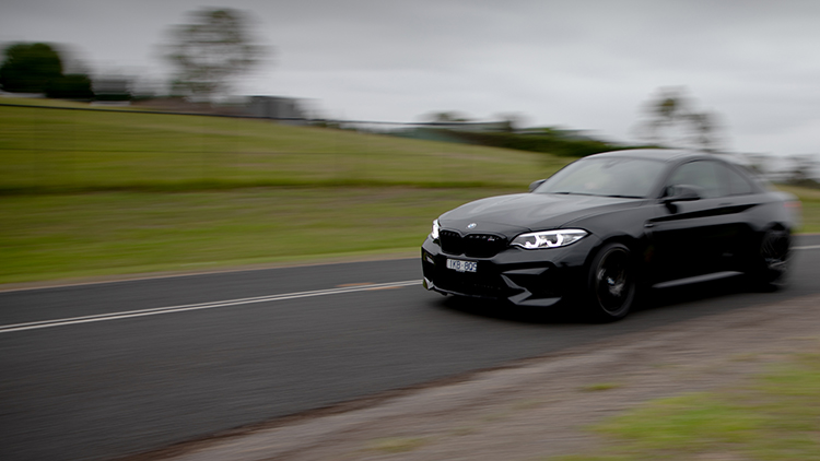 BMW M2 Competition, in black, driving from right to left of frame along a country road