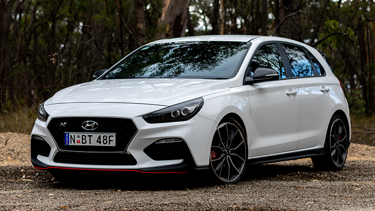 Front 3/4 view of a white Hyundai i30 N with the front wheels slightly turned for effect.