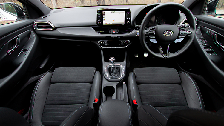 Wide angle shot of a cars dashboard. Media screen in the middle, steering wheel on the right.