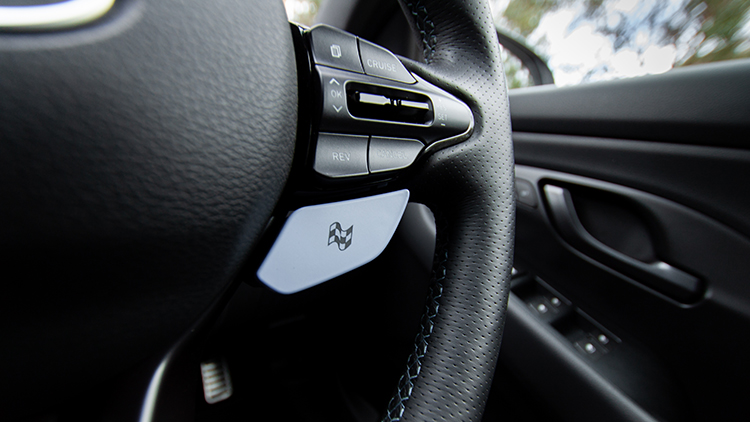 Bottom right-hand corner of steering wheel where there's a power-blue coloured button with a chequered flag icon on it.