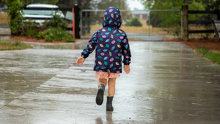Young child wearing pink shorts, gumboots and a blue/purple raincoat running up a concrete driveway away from the camera.