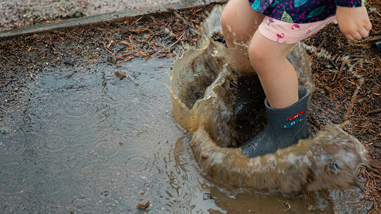 Close up of young girl jumping into a puddle making a big splash