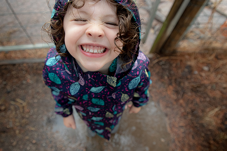 Three-year old girl standing in a puddle looking up at the camera with a big smile on her face.